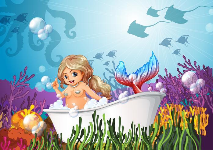 Een badkuip onder de zee met een zeemeermin