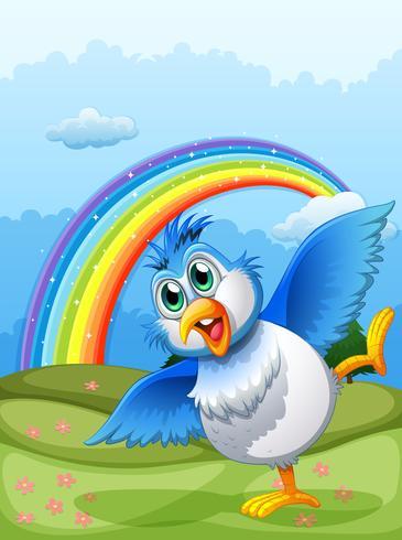 Un pájaro lindo en la cima de la colina con un arco iris en el cielo