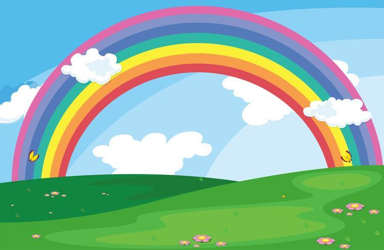 Ett grönt landskap med en regnbåge i himlen