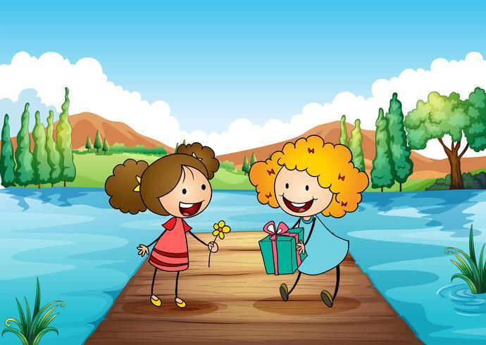 Två söta tjejer utbyter gåvor vid floden