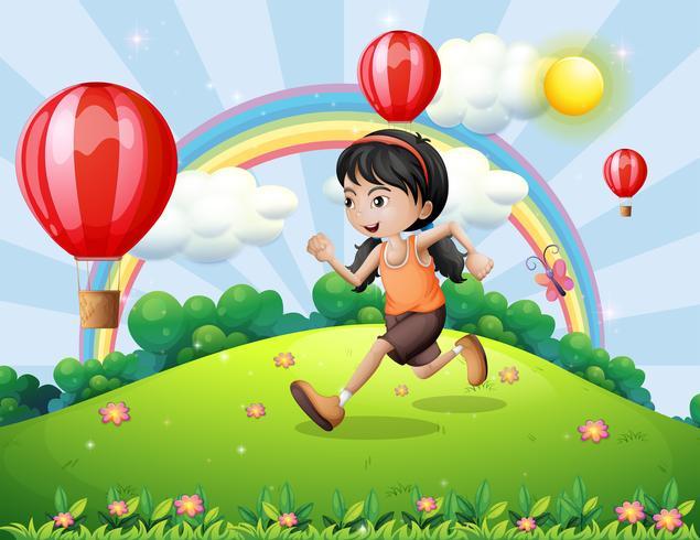 Una niña corriendo en la cima de la colina.