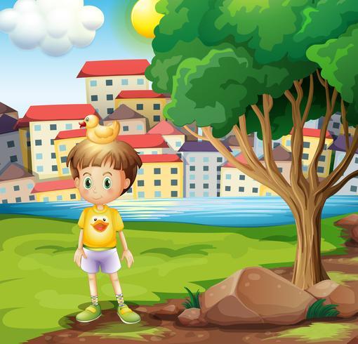 Un ragazzo con un'anatra di gomma sopra la sua testa in piedi vicino all'albero