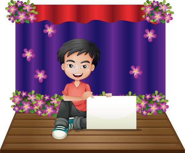 Un jeune garçon souriant assis au milieu de la scène tenant un affichage vide