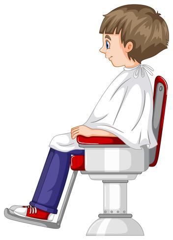 El niño pequeño se sienta en la silla de peluquero