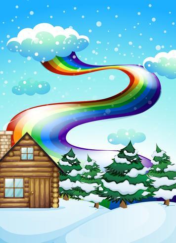 Una casa de madera cerca de los pinos con un arco iris en lo alto.