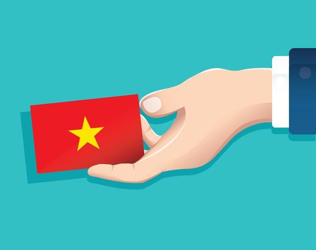 Hand, die Vietnam-Flaggenkarte mit blauem Hintergrund hält