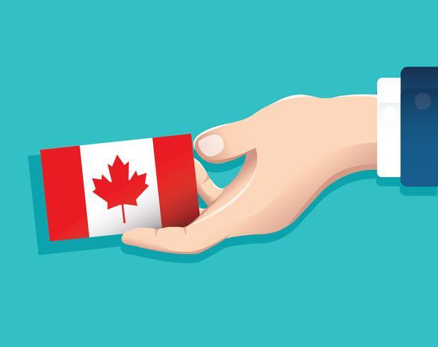 mão segurando o cartão de bandeira do Canadá com fundo azul