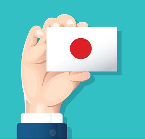 Mano Che Tiene La Carta Della Bandiera Del Giappone Con Sfondo Blu