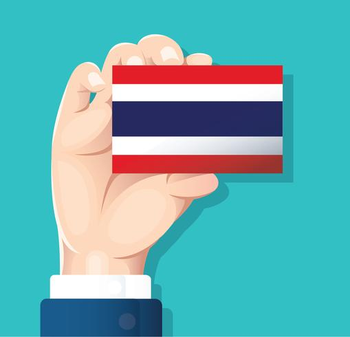mano que sostiene la tarjeta de la bandera de Tailandia con fondo azul