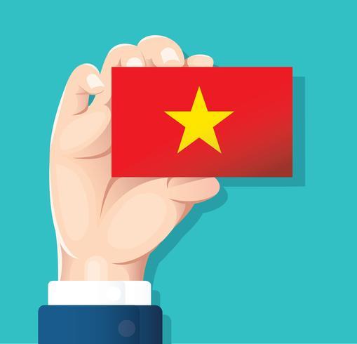 mano que sostiene la tarjeta de la bandera de vietnam con fondo azul