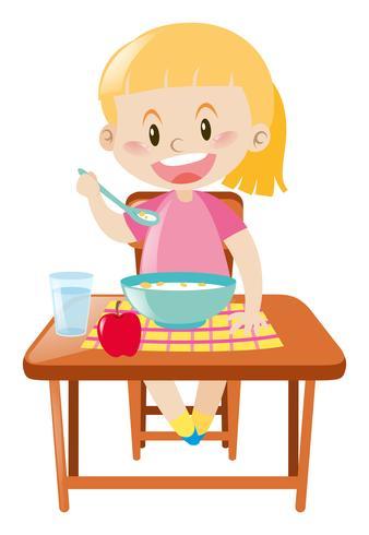 Menina feliz tomando café da manhã