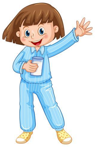 Menina de pijama azul com copo de leite