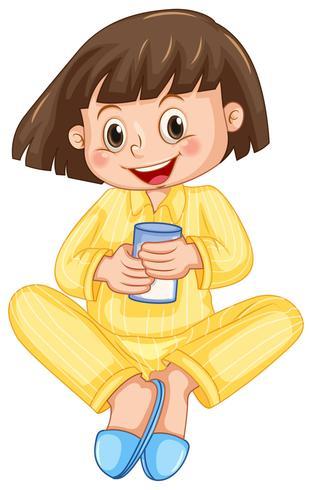 Liten flicka i gul pyjamas drickmjölk
