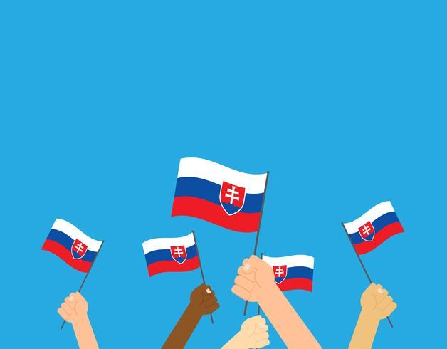 Handen die de vlaggen van Slowakije houden die op blauwe achtergrond worden geïsoleerd