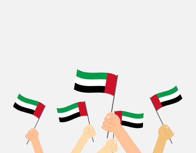 Vector die Illustrationshände, die Flaggen der Vereinigten Arabischen Emirate auf weißem Hintergrund halten