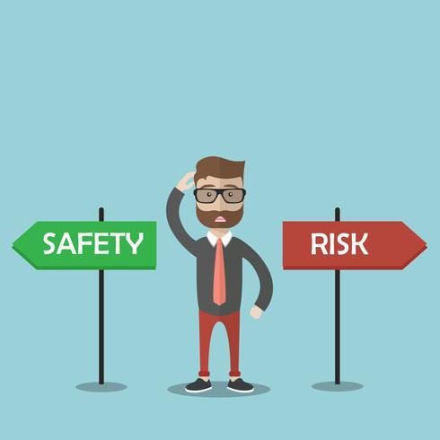 Uomo d'affari confuso che sta accanto ai segni di rischio e di sicurezza