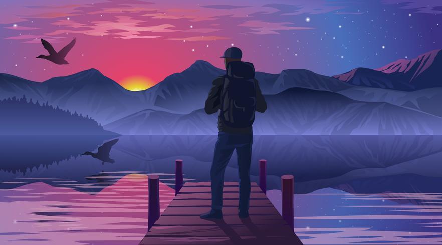 Man på piren beundrar solnedgången