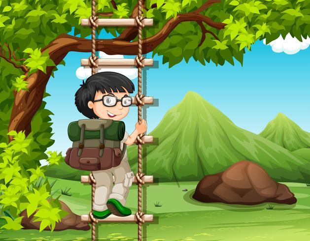 Ragazzo che sale la scala di legno in parco