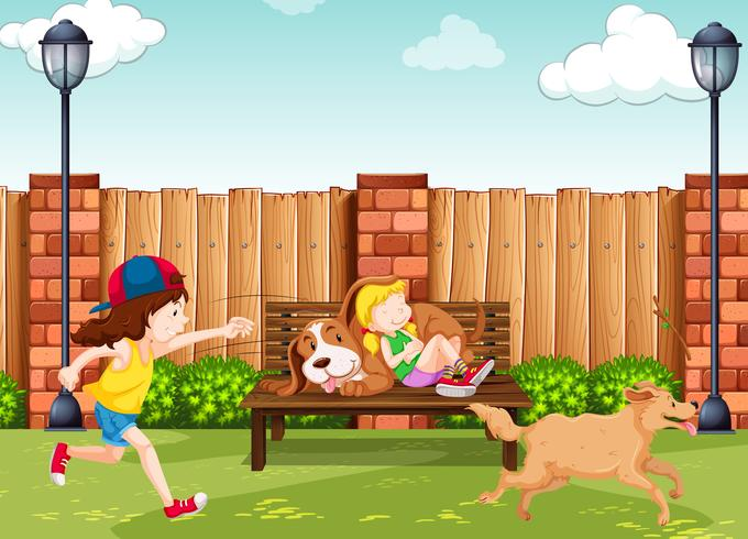 Filles jouant avec des chiens dans le parc