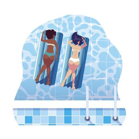 Hermosas chicas interraciales con colchón flotador en agua.