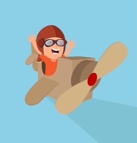 Niño jugando como piloto con avión de cartón