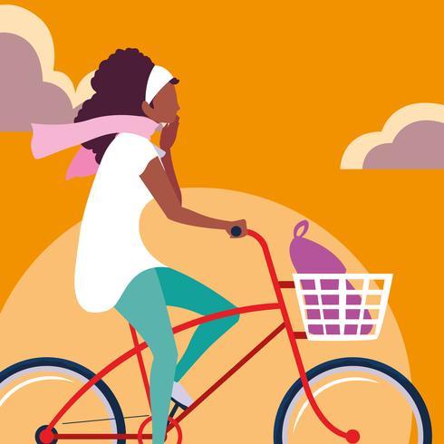 jeune femme afro à vélo avec ciel orange vecteur