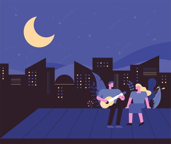 Notte in città con un uomo che suona la chitarra con la sua ragazza sul tetto