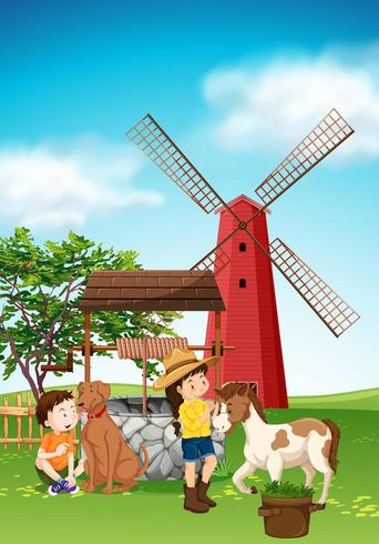 Bambini e animali nel cortile con mulino a vento vettore