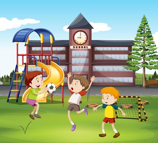 Tre pojkar som spelar fotboll framför skolan