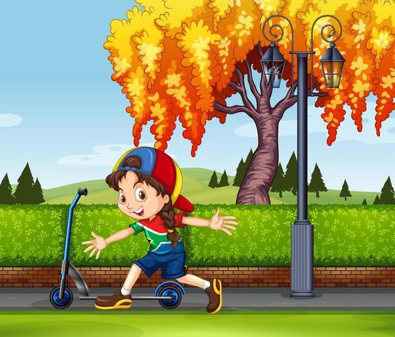 Bambina con scooter nel parco