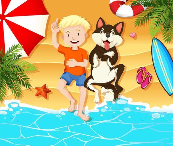Luftaufnahme des Jungen und des Hundes, die auf dem Strand stillstehen