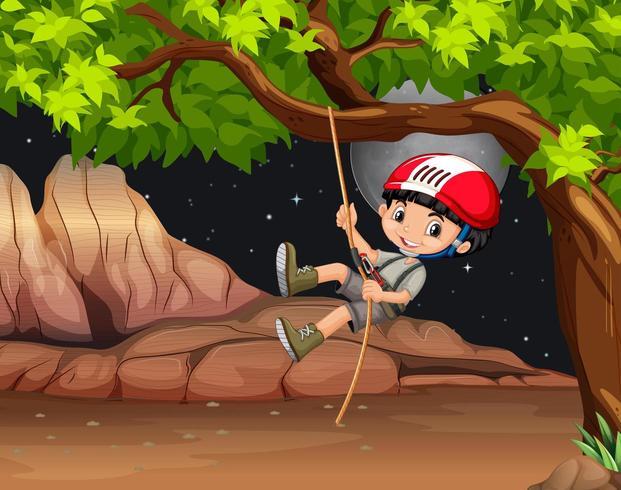 Ragazzo che arrampica un albero di notte