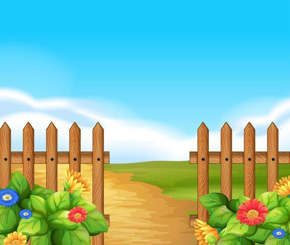 Escena con valla de madera y campo con flores.