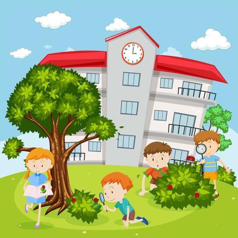 Bambini che esaminano gli insetti nel cortile della scuola