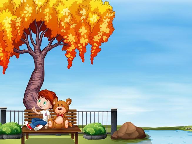 Jongen en teddybeer in het park