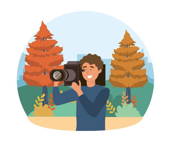 Cameraman in park with pine trees