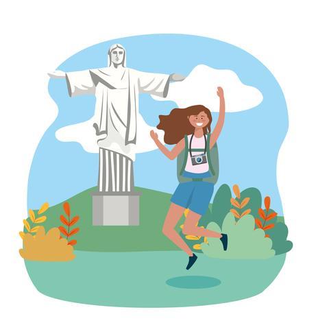 Mujer saltando con la estatua del Cristo Redentor en segundo plano.