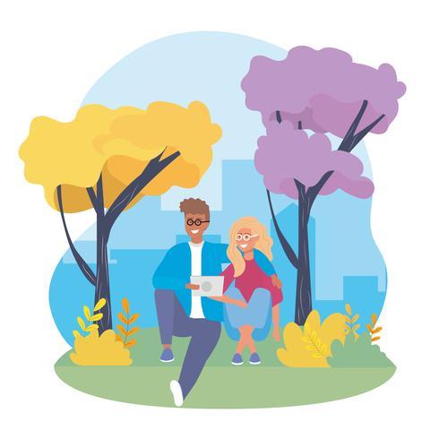 Junge Paare mit der Tablette, die im Park sitzt