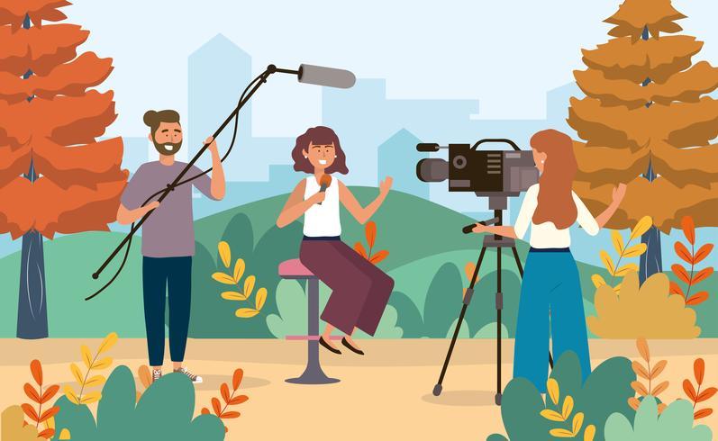 Reportero con micrófono y camarógrafa en el parque
