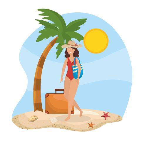 Mujer en traje de baño en la playa con bolsa y maleta