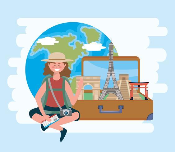 Weiblicher Tourist im Hut mit Koffer mit Marksteinen