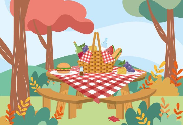 Cesta de picnic con mantel y comida en la mesa en el parque