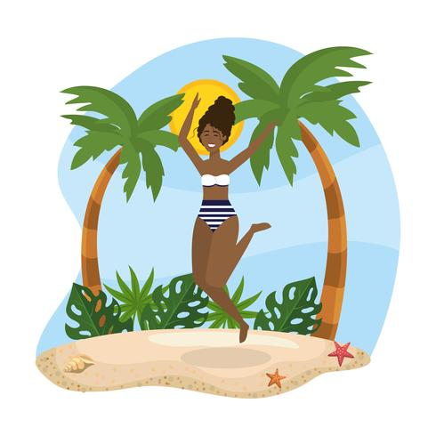 La giovane donna che salta vicino alle palme sulla sabbia
