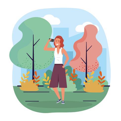 Donna con lo smartphone che cammina nel parco