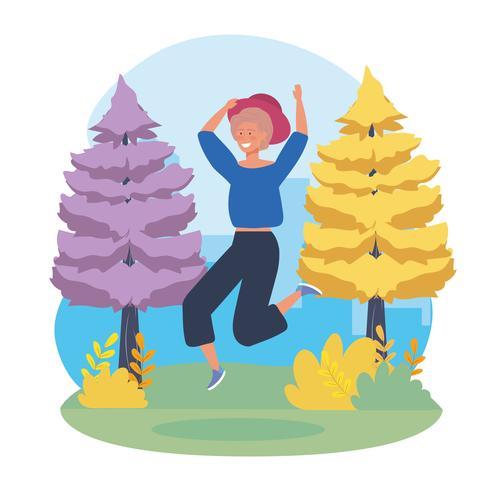Giovane donna con cappello saltando nel parco