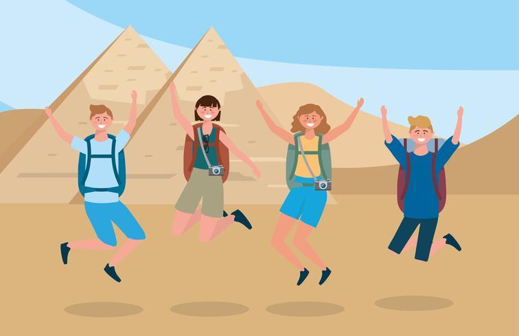 Turistas masculinos y femeninos saltando delante de las pirámides egipcias