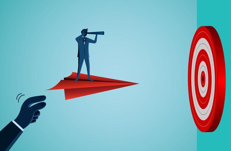 Um homem de negócios de pé em um avião de papel voando para o alvo