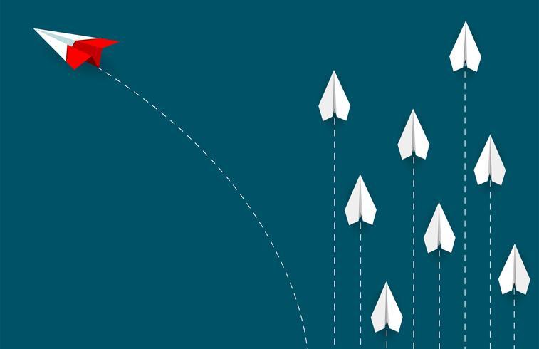 Ändernde Richtung des roten Papierflugzeuges vom Weiß