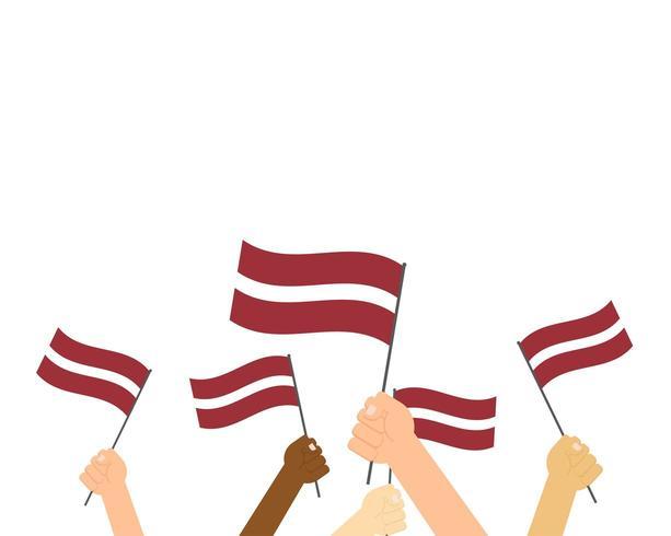 Handen met vlaggen van Letland