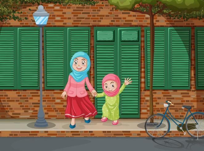 Muslim girls holding hands on the sidewalk